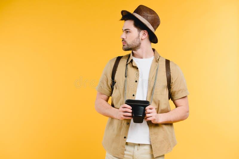 jeune homme dans le chapeau avec la caméra et le regard de participation de sac à dos loin photos libres de droits