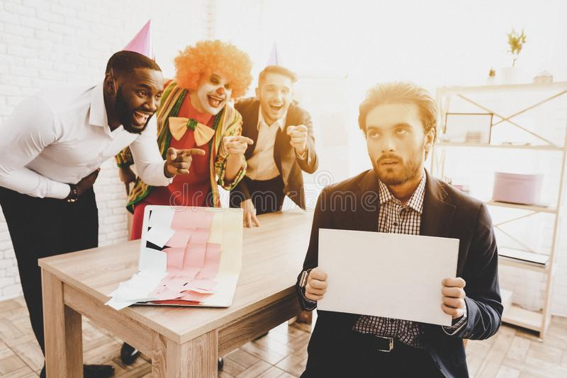 Jeune homme dans le clown Costume sur la réunion dans le bureau photos stock