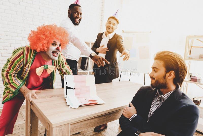Jeune homme dans le clown Costume sur la réunion dans le bureau photos libres de droits