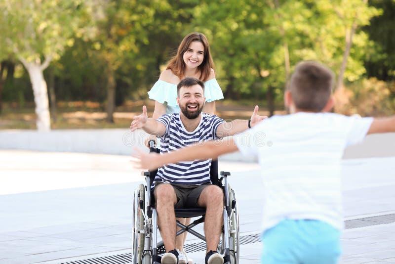 Jeune homme dans le fauteuil roulant jouant avec son fils dehors image libre de droits