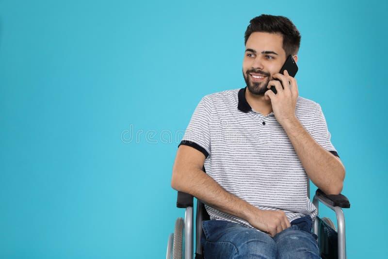 Jeune homme dans le fauteuil roulant parlant au t?l?phone sur le fond de couleur photo stock