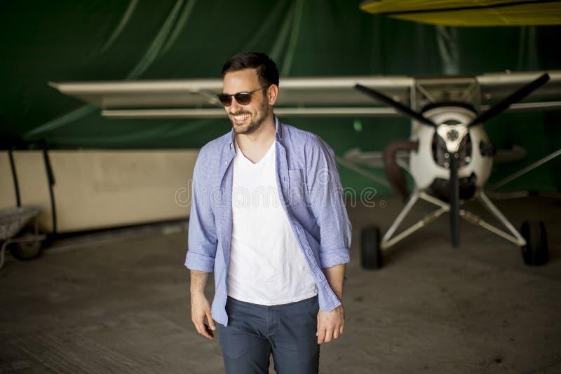 Jeune homme dans le hangar d'avion photos stock