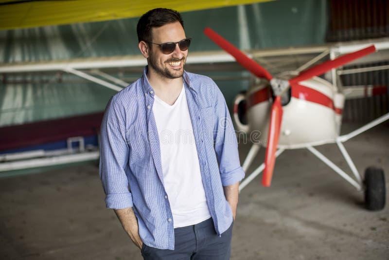 Jeune homme dans le hangar d'avion photographie stock