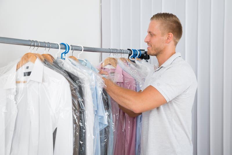 Jeune homme dans le magasin de nettoyage à sec photo stock