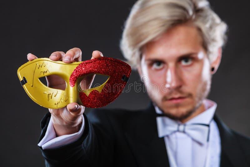 Jeune homme dans le masque de carnaval sur l'obscurité image stock