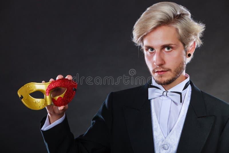 Jeune homme dans le masque de carnaval sur l'obscurité images stock