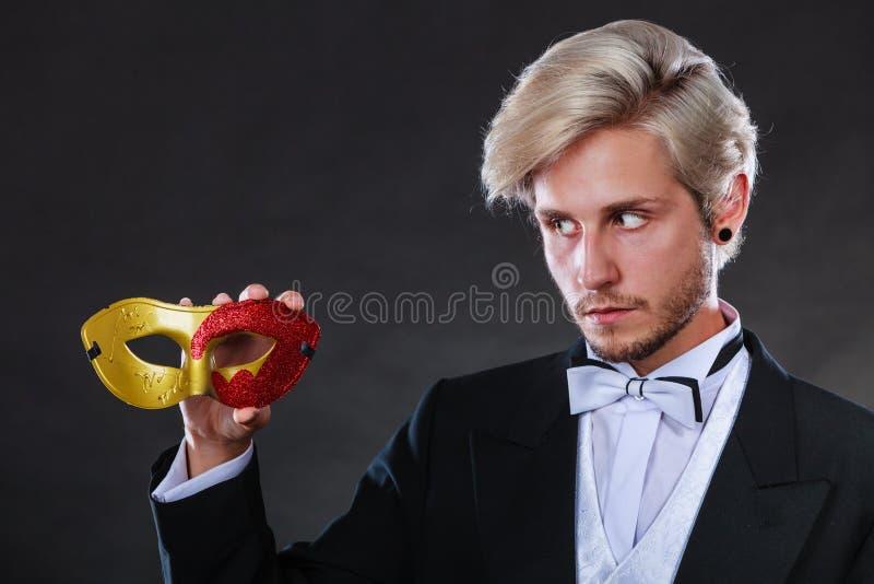 Jeune homme dans le masque de carnaval sur l'obscurité photos stock