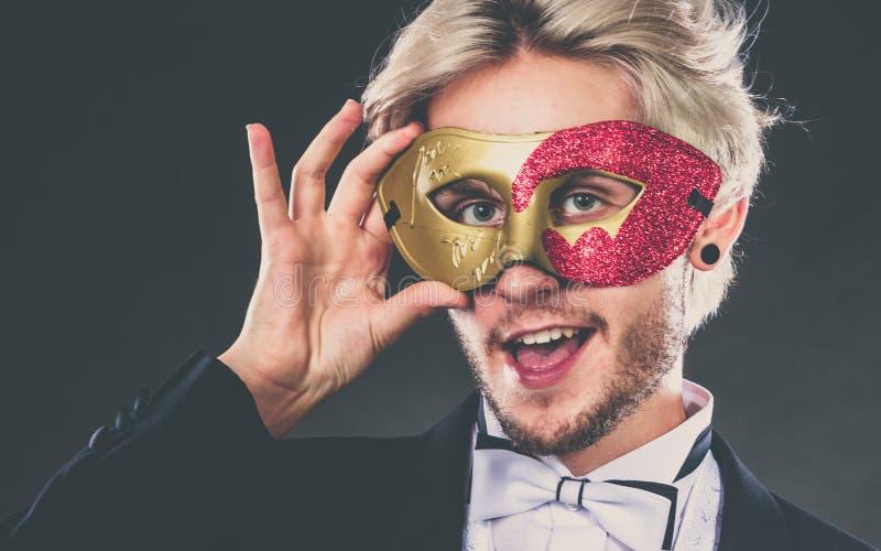 Jeune homme dans le masque de carnaval sur l'obscurit? images libres de droits