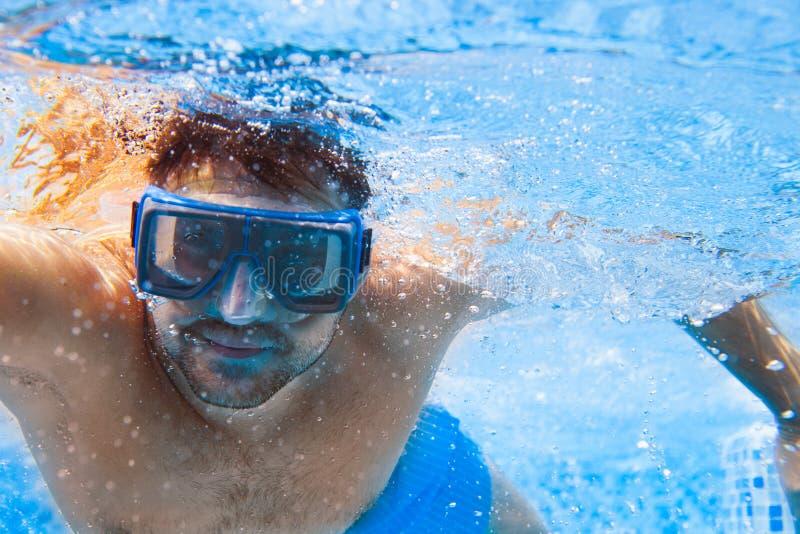 Jeune homme dans le masque de plongée nageant le rampement avant dans une piscine, tak images libres de droits