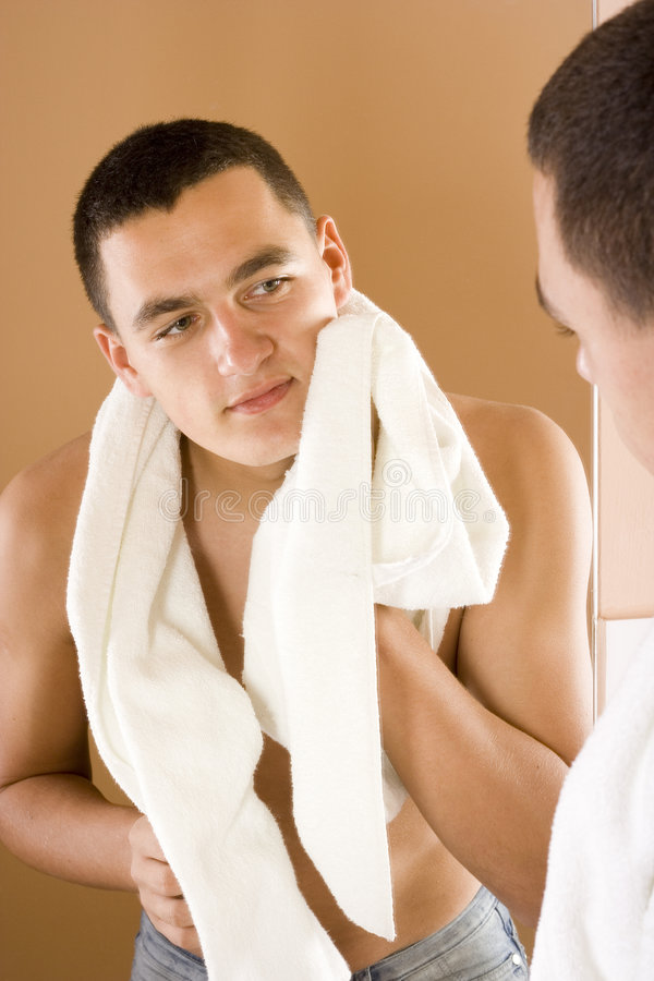 Jeune homme dans le miroir de la salle de bains après avoir rasé photographie stock