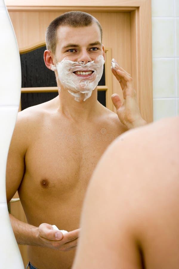 Jeune homme dans le miroir de la salle de bains avec de la mousse de rasage sur le visage photo libre de droits