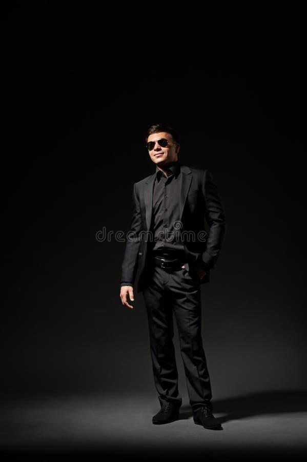 Jeune homme dans le procès et des lunettes de soleil noirs image libre de droits
