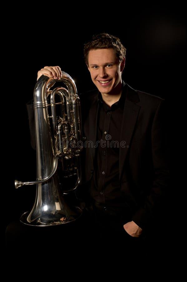 Jeune homme dans le procès retenant un klaxon de trompette image stock