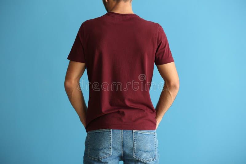 Jeune homme dans le T-shirt élégant sur le fond de couleur, vue de dos photographie stock libre de droits