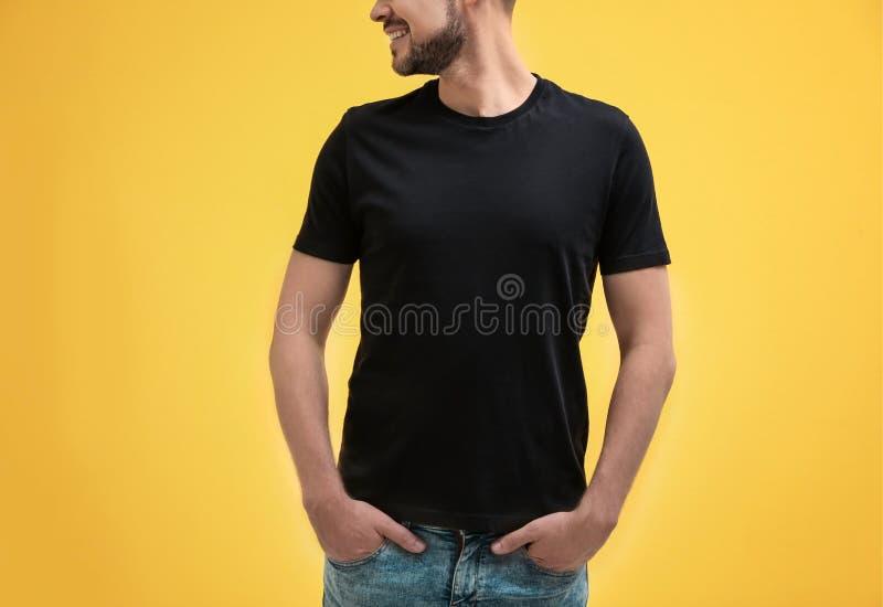 Jeune homme dans le T-shirt noir sur la maquette de fond de couleur pour la conception photos libres de droits