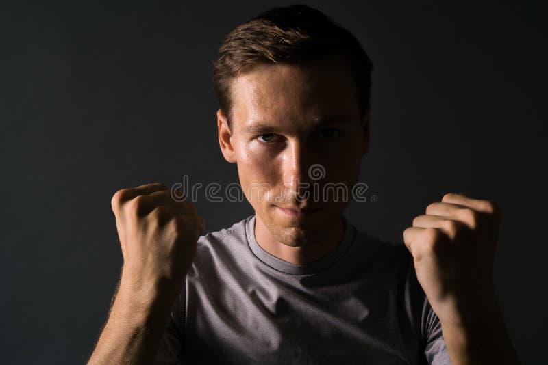 Jeune homme dans le T-shirt sur un fond foncé tenant des poings à son visage photo libre de droits