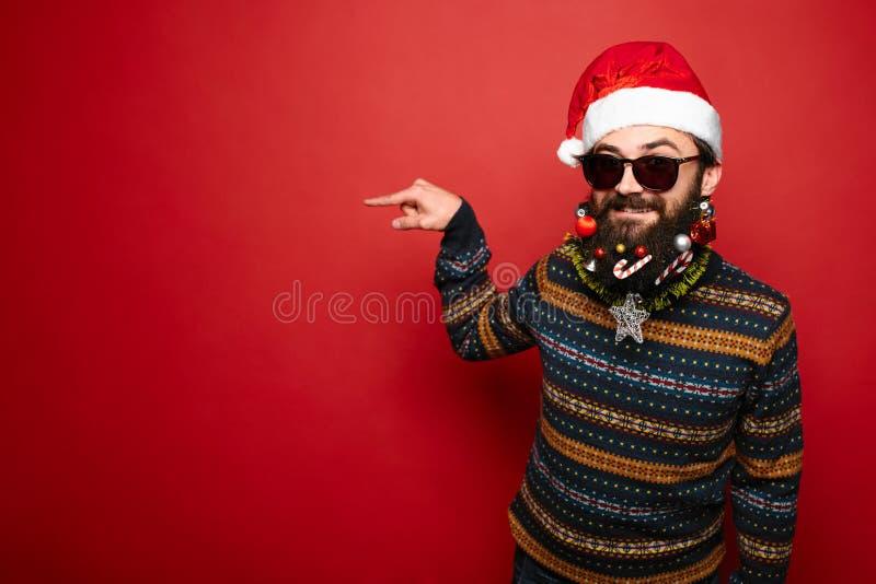 Jeune homme dans les lunettes de soleil et le chapeau de Santa se dirigeant loin photos libres de droits