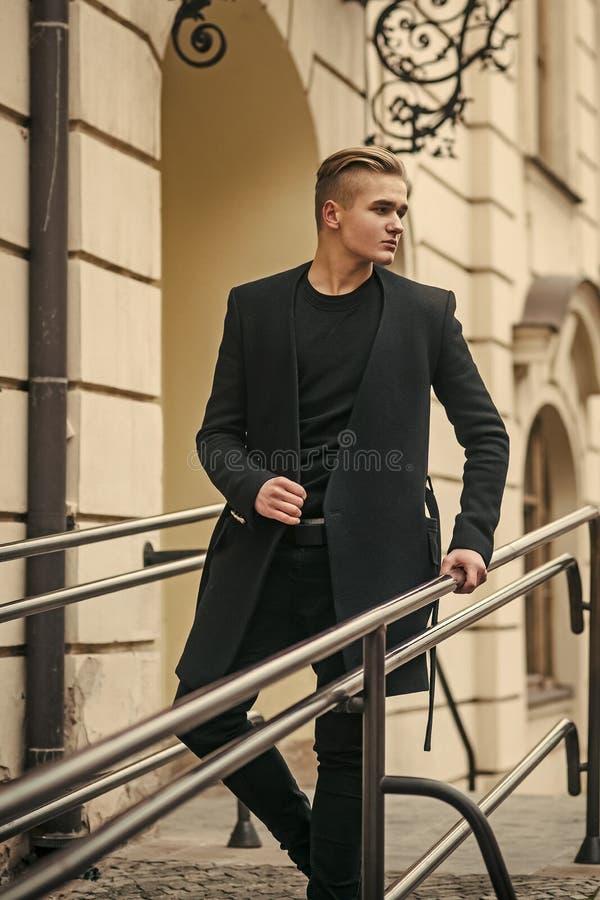 Jeune homme dans les promenades noires d'équipement dans la vieille ville photos libres de droits