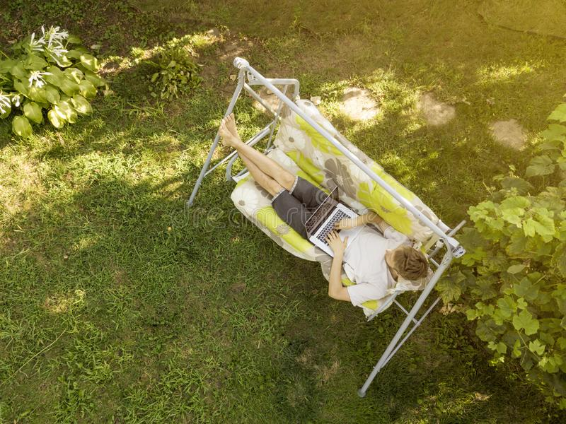 Jeune homme dans se situer occasionnel dans le divan travaillant sur l'ordinateur portable des vacances d'été photographie stock