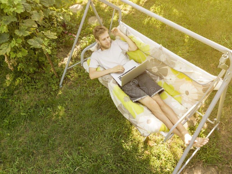 Jeune homme dans se situer occasionnel dans le divan travaillant sur l'ordinateur portable des vacances d'été photo libre de droits