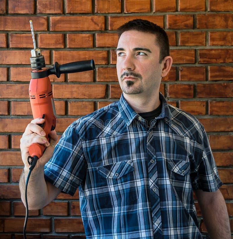 Jeune homme dans son 30s tenant un foret électrique rouge photos stock