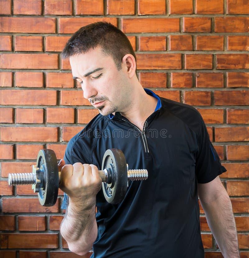 Jeune homme dans son 30s tirant le dumbell image stock