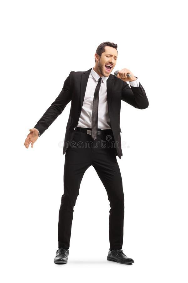 Jeune homme dans un costume chantant sur une MIC image stock