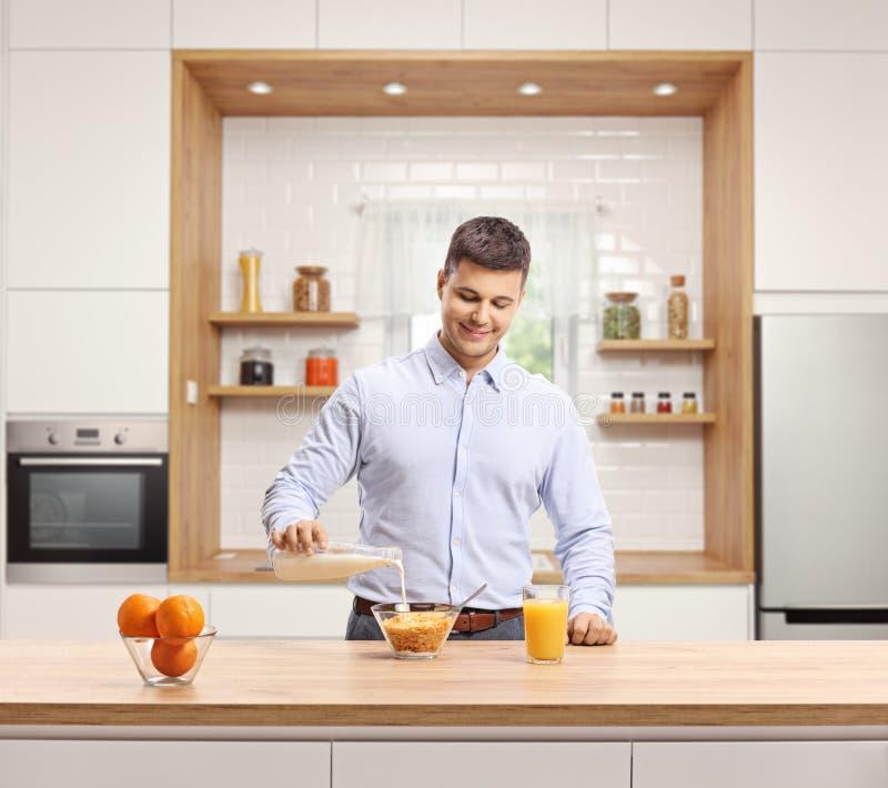 Jeune homme dans un lait se renversant de chemise dans un bol de céréale pour le petit déjeuner dans une cuisine moderne photo stock