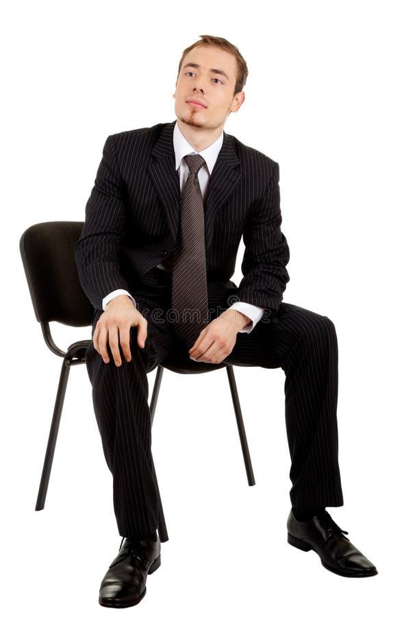 Jeune homme dans un procès noir d'affaires se reposant sur un ch photos stock
