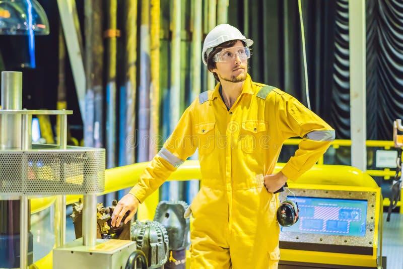Jeune homme dans un uniforme jaune, les verres et le casque de travail dans le milieu industriel, la plateforme p?troli?re ou l'u images stock