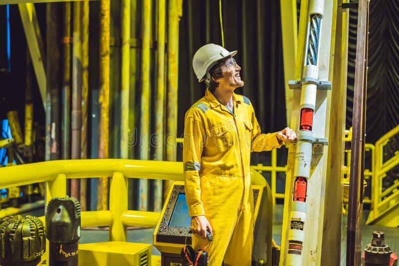 Jeune homme dans un uniforme jaune, les verres et le casque de travail dans le milieu industriel, la plateforme p?troli?re ou l'u images libres de droits