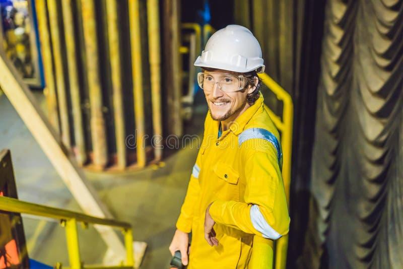 Jeune homme dans un uniforme jaune, les verres et le casque de travail dans le milieu industriel, la plateforme p?troli?re ou l'u image libre de droits