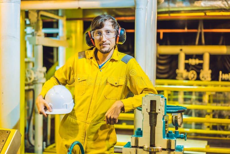 Jeune homme dans un uniforme jaune, les verres et le casque de travail dans le milieu industriel, la plateforme p?troli?re ou l'u image stock