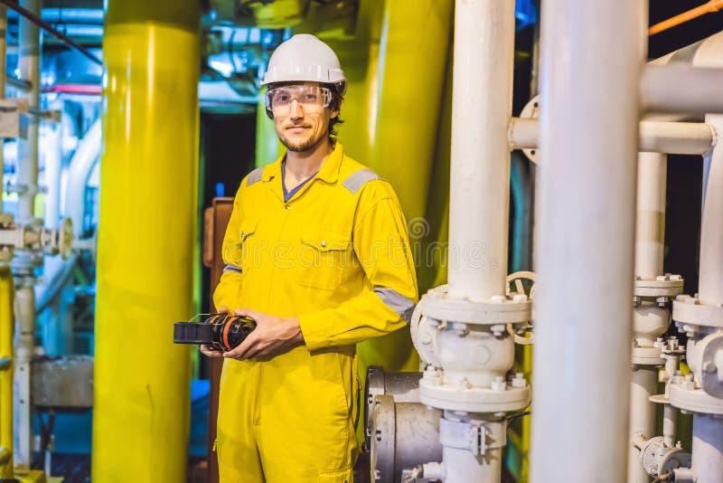 Jeune homme dans un uniforme jaune, les verres et le casque de travail dans le milieu industriel, la plateforme p?troli?re ou l'u photo libre de droits