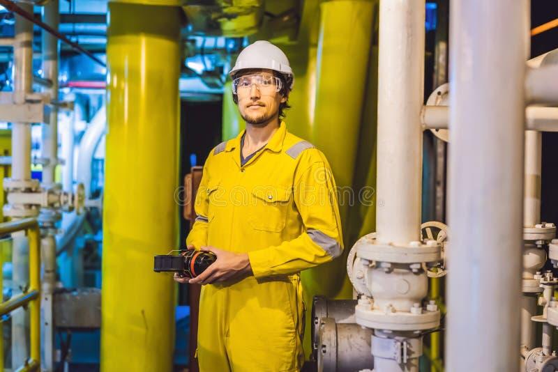 Jeune homme dans un uniforme jaune, les verres et le casque de travail dans le milieu industriel, la plateforme p?troli?re ou l'u photographie stock libre de droits