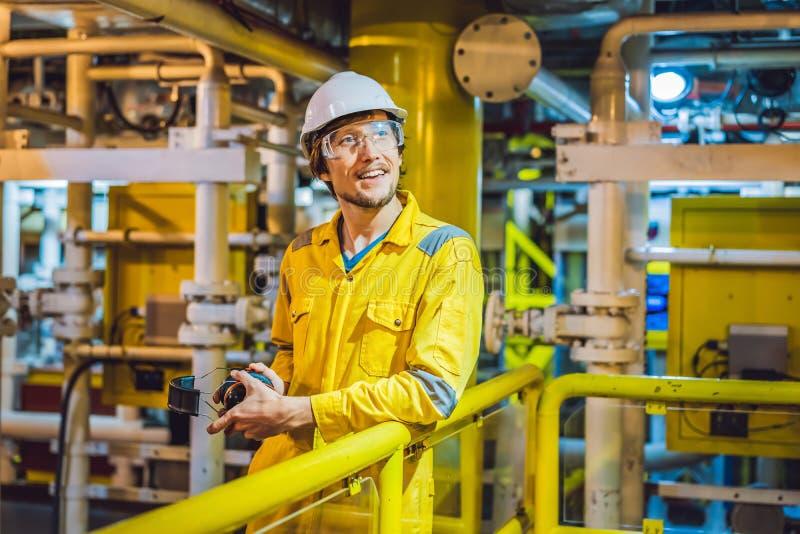 Jeune homme dans un uniforme jaune, les verres et le casque de travail dans le milieu industriel, la plateforme p?troli?re ou l'u photographie stock