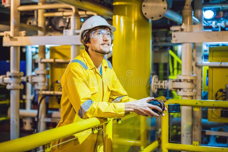 Jeune homme dans un uniforme jaune, les verres et le casque de travail dans le milieu industriel, la plateforme p?troli?re ou l'u photo stock