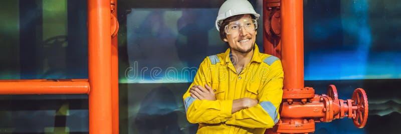 Jeune homme dans un uniforme jaune, les verres et le casque de travail dans le milieu industriel, la plateforme p?troli?re ou l'u photos libres de droits