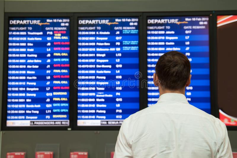 Jeune homme dans une chemise avec une valise dans l'aéroport près de l'horaire de vol photographie stock libre de droits
