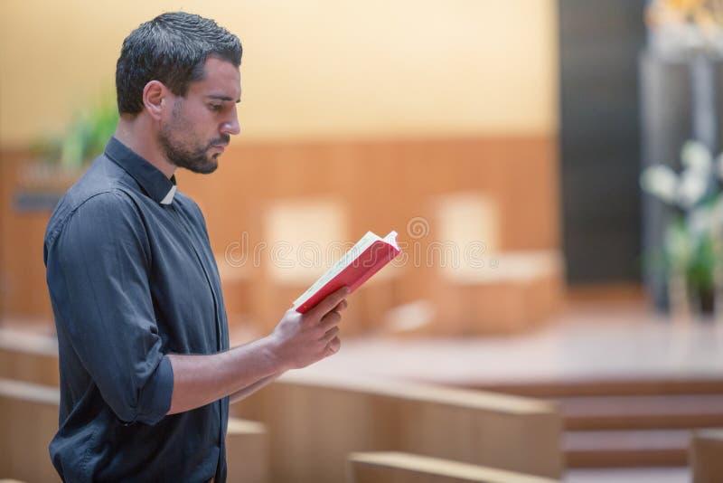 Jeune homme de barbe utilisant la chemise bleue priant avec la bible dans l'église moderne images libres de droits