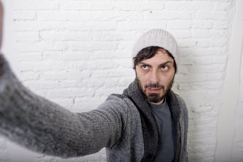 Jeune homme de blogger de hippie tenant la photo ou la vidéo de selfie de tir de téléphone portable d'écran photos libres de droits