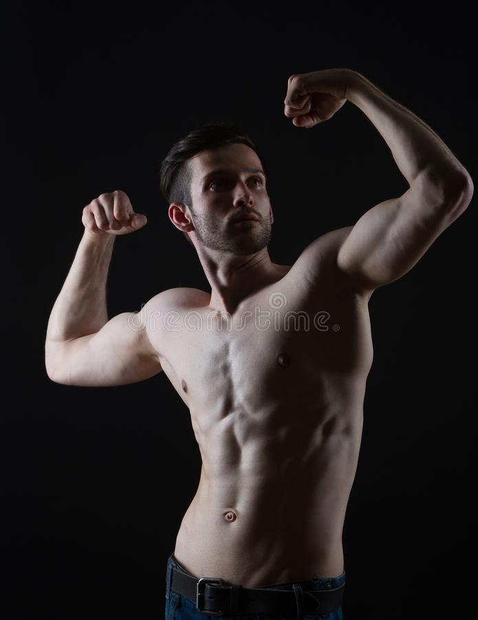 Jeune homme de bodybuilding avec des muscles sur le fond noir images libres de droits