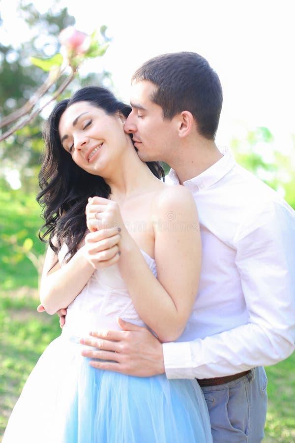 Jeune homme de brune étreignant et embrassant la fille caucasienne en parc photographie stock libre de droits