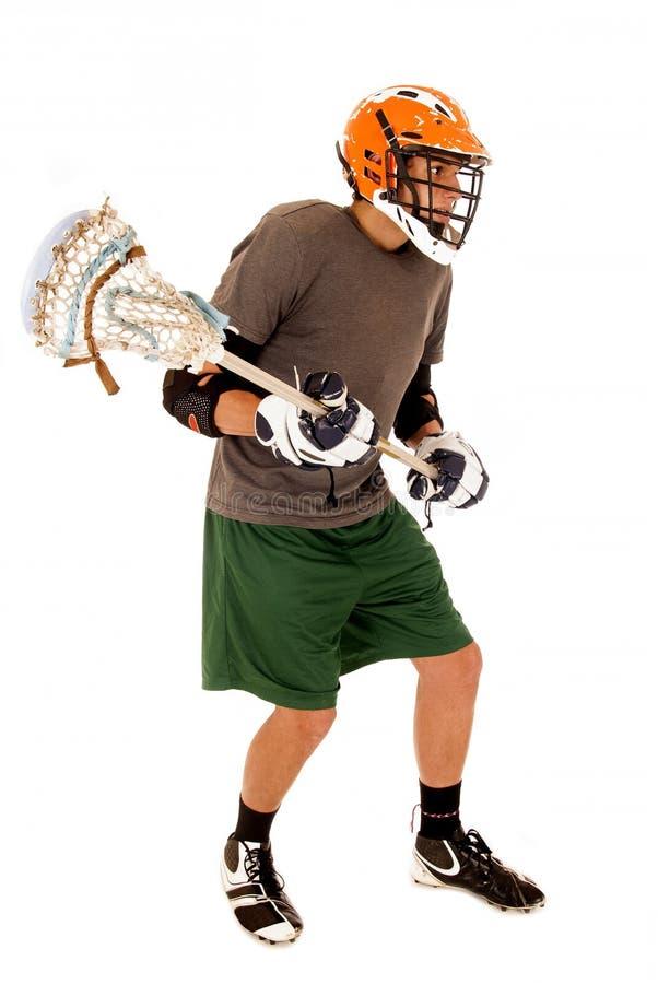 Jeune homme de brune dans le bâton se tenant uniforme de lacrosse photographie stock libre de droits