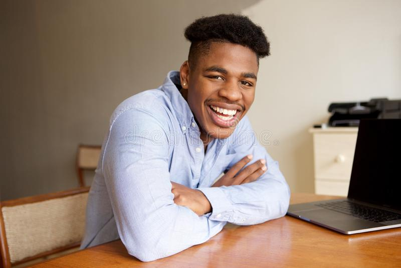 Jeune homme de charme d'afro-américain s'asseyant au bureau avec l'ordinateur portable photo libre de droits