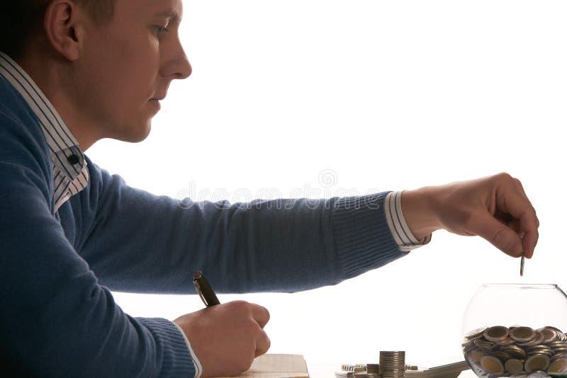 Jeune homme de comptable mettant la pièce de monnaie dans la tirelire en verre photographie stock
