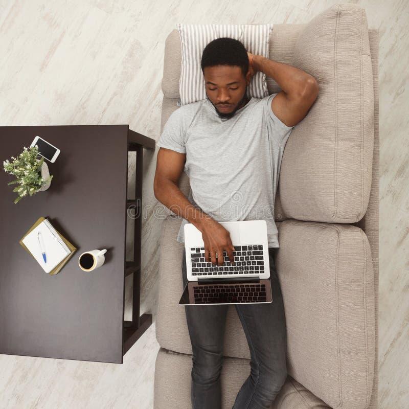 Jeune homme de Concenrated à l'aide de l'ordinateur portable à la maison image libre de droits