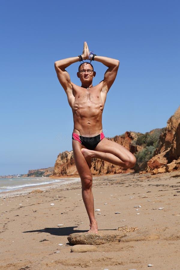 Jeune homme de construction sportive dans la pose de yoga d'arbre photos libres de droits