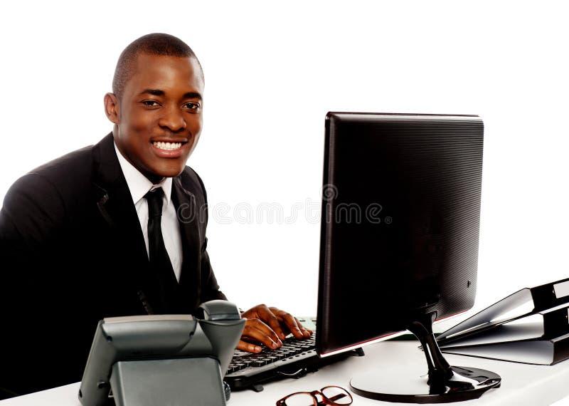 Jeune homme de corporation de sourire à l'aide de l'ordinateur image libre de droits