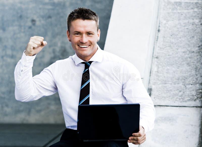 Jeune homme de corporation exalté avec l'ordinateur portatif photographie stock libre de droits